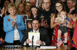 Arizona Republican Gov. Doug Ducey, middle, smiles after signing into law a bill regarding distracted driving as he is joined by legislators, like bill sponsor Kate Brophy McGee, left, R-Phoenix, members of law enforcement and family members of victims of distracted drivers, during a ceremony at the Arizona Capitol Monday, April 22, 2019, in Phoenix