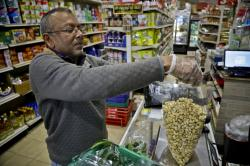 "Dhannitha Meemanage, from Sri Lanka, bags cashews in his family's grocery store, in New York's Staten Island's ""Little Sri Lanka"" community, Monday, April 22, 2019"