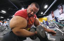 Egyptian body builder Moustafa Ismail lifts free weights during his daily workout in Milford, Mass.