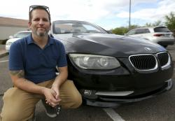 In this April 23, 2019, photo, Chris Williamson poses for a photo sitting next to his car in Phoenix