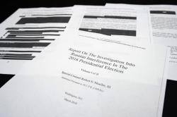 Four pages of the Mueller Report lay on a witness table in the House Intelligence Committee hearing room on Capitol Hill, in Washington, Thursday, April 18, 2019