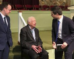 Democratic presidential candidate Pete Buttigieg, right, and his husband, Chasten Glezman, left, speak with former President Jimmy Carter.