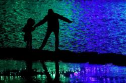 In this Nov. 30, 2018, file photo people are silhouetted against holiday lights reflecting off a pond in a park in Lenexa, Kan.