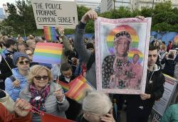 Participants in a protest hold copies of the posters and a giant rainbow flag in support of Elzbieta Podlesna, in Warsaw, Poland.