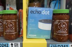 This Dec. 20, 2017, file photo shows the Amazon Echo Dot stocked on a shelf alongside jars of Garlic Chili Sauce at the Amazon Prime warehouse in New York