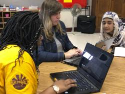 In this April 16, 2019, photo, eighth grade student technicians Mirakle Singleton, left, and Naureen Unaysa, right, instruct teacher Kaila Burgio in the use of a computer program at Buffalo Public School No. 37, in Buffalo, N.Y.