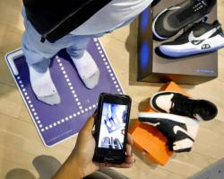 Nike officials demonstrate the company's foot-scanning tool on its app.