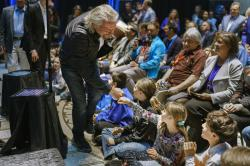 Virgin Galactic founder Richard Branson, gives a fist bump to Sonia Thorp, 9, of Carlos Gilbert Elementary at the beginning of an event at the state capital on Friday, May 10, 2019, in Santa Fe, N.M.