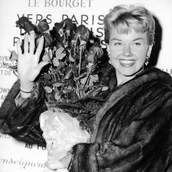 Doris Day holds a bouquet of roses at Le Bourget Airport in Paris, France after flying in from London in 1955.