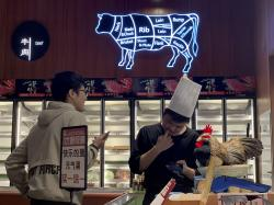 A worker at the imported beef section of a supermarket that used to carry U.S. products chats with another in Beijing on Tuesday, May 14, 2019