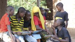 In this undated photo provided by XPRIZE, children in a village in the Tanga region of Tanzania gather to learn from tablets using open-sourced software that would easily be downloaded by illiterate children to teach themselves to read