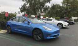 This undated photo provided by Edmunds shows a 2017 Tesla Model 3 at one of the many supercharger stations across the country