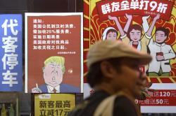 In this Aug. 13, 2018, file photo, a man walks by a poster depicting a mural of U.S. President Donald Trump