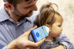 In this undated photo provided by the University of Washington in May 2019, Dr. Randall Bly uses a uses a phone app and a paper funnel to focus the sound, to check his daughter for an ear infection, at the UW School of Medicine in Seattle