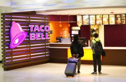 Travelers look at a menu at a Taco Bell restaurant inside Miami International Airport in Miami.
