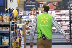 A Walmart associate works at a Walmart Neighborhood Market in Levittown, N.Y.