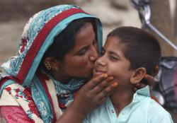A Pakistani mother kisses her son Ali Raza, 10, infected with HIV in a village near Ratodero.
