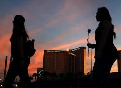 In this April 1, 2018, file photo, people carry flowers as they walk near the Mandalay Bay hotel and casino during a vigil for victims and survivors of a mass shooting in Las Vegas