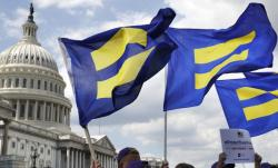 """In this Wednesday, July 26, 2017 file photo, people with the Human Rights Campaign hold up """"equality flag."""""""