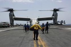In this Friday, May 17, 2019, photo, released by the U.S. Navy, sailors work around an MV-22 Osprey as it lands on the flight deck of the Nimitz-class aircraft carrier USS Abraham Lincoln.