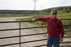 In this April 8, 2019, photo, Tim Tanksley, who has been fighting for years trying to convince Oklahoma lawmakers to crack down on the coal ash dumping, stands outside a dump site in Bokoshe, Okla.