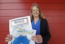 In this photo taken Wednesday, May 15, 2019, Vashon Island High School nurse Sarah Day holds information about measles vaccinations as she poses for a photo in Vashon Island, Wash.