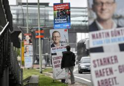 In this Thursday, May 16, 2019 photo, a man stands in fron of posters for the European and state elections of Social Democrats, SPD, and Alternative for Germany, AfD, in Bremerhaven, Germany