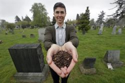 In this April 19, 2019, file photo, Katrina Spade, the founder and CEO of Recompose, a company that hopes to use composting as an alternative to burying or cremating human remains, poses for a photo in a cemetery in Seattle, as she displays a sample of compost material left from the decomposition of a cow using a combination of wood chips, alfalfa and straw