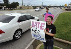 Jessica Morgan, 19, of Whitehouse, Texas, and Bobby Ortiz, 18, of Whitehouse, hold signs supporting gay marriage outside of Chick-fil-A in Tyler, Texas.