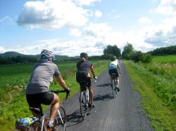 Cyclists on Velo Quebec's Grand Tour sweep along a trail in the Eastern Townships.