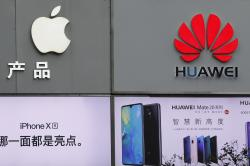 In this Thursday, March 7, 2019, file photo, logos of Apple and Huawei are displayed outside a mobile phone retail shop in Shenzhen, China's Guangdong province.