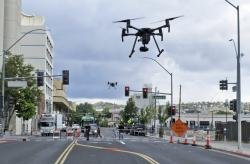 In this May 21, 2019 photo, two drones fly above Lake Street in downtown Reno, Nev., on, as part of a NASA simulation to test emerging technology that someday will be used to manage travel of hundreds of thousands of commercial, unmanned aerial vehicles (UAVs) delivering packages