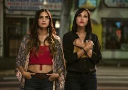 """This image released by Starz shows Melissa Barrera, left, and Mishel Prada from the series """"Vida,"""" a drama that follows two Mexican American sisters battling gentrification and the aftermath of their mother's death. (Kat Marcinowski/Starz via AP)"""