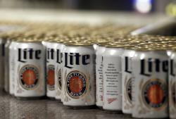 In this March 11, 2015 file photo, newly-filled and sealed cans of Miller Lite beer move along on a conveyor belt, at the MillerCoors Brewery, in Golden, Colo.