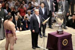 "President Donald Trump, center, speaks as Trump presents the ""President's Cup"" trophy to the Tokyo Grand Sumo Tournament winner Asanoyama, left, at Ryogoku Kokugikan Stadium."
