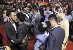 Taiwanese same-sex couples kiss at their wedding party in Taipei, Taiwan.