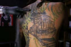 "A tattoo artist known as Enrique inks the image of the train known as ""La Bestia"" on the arm of a migrant from El Salvador."