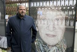 Artist Luigi Toscano stands next to destroyed and repaired pictures showing Holocaust survivors in Vienna, Austria, Tuesday, May 28, 2019