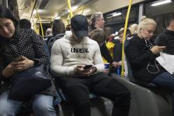 Passengers look at their smartphones as they ride a bus in Moscow, Russia.