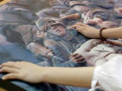 Sophie Trist, of the New Orleans chapter of the National Federation of the Blind, touches a bass relief of a photograph of the Vietnam Tet Offensive, by John Olson, whose company 3DPhotoworks also makes the bass relief, at the American Alliance of Museums Expo in New Orleans, Monday, May 20, 2019