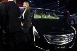 In this April 19, 2015, file photo General Motors CEO Mary Barra stands next to the Cadillac CT6 luxury sedan during a General Motors event ahead of the Auto Shanghai show in Shanghai, China