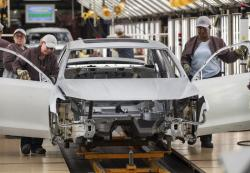 In this Aug. 31, 2017, file photo, workers produce vehicles at Volkswagen's U.S. plant in Chattanooga, Tenn.