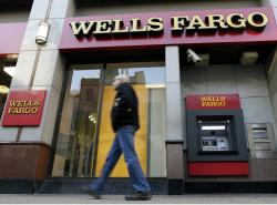 In this Dec. 19, 2012, file photo, a man walks past a Wells Fargo branch in Philadelphia