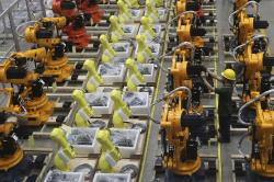 A worker checks on robot arms at a factory in Nanjing in east China's Jiangsu province, Thursday, June 6, 2019