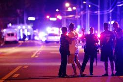 An Orlando Police officer directs family members away from a mass shooting at the Pulse nightclub in Orlando, Fla.