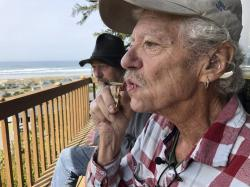 In this April 25, 2019, photo, two-time cancer survivor and medical marijuana cardholder Bill Blazina, 73, smokes a marijuana joint on the deck of his neighbor's home in Waldport, Ore.