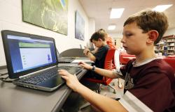 In this May 8, 2019, photo, third-grade student Miles Stidham uses an East Webster High School laptop to do homework in Maben, Miss.