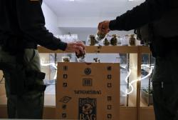 In this March 15, 2018 file photo, two undercover Los Angeles County sheriff's deputies dump marijuana into an evidence bag during a raid at an illegal marijuana dispensary during a raid in Compton, Calif.
