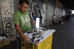Levis Villamil repairs broken lightbulbs at his street stand for customers who can't afford new ones in Caracas, Venezuela, Monday, May 13, 2019
