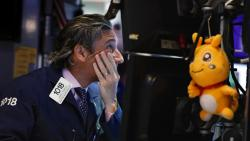 In this May 29, 2019, file photo trader John Romolo works on the floor of the New York Stock Exchange